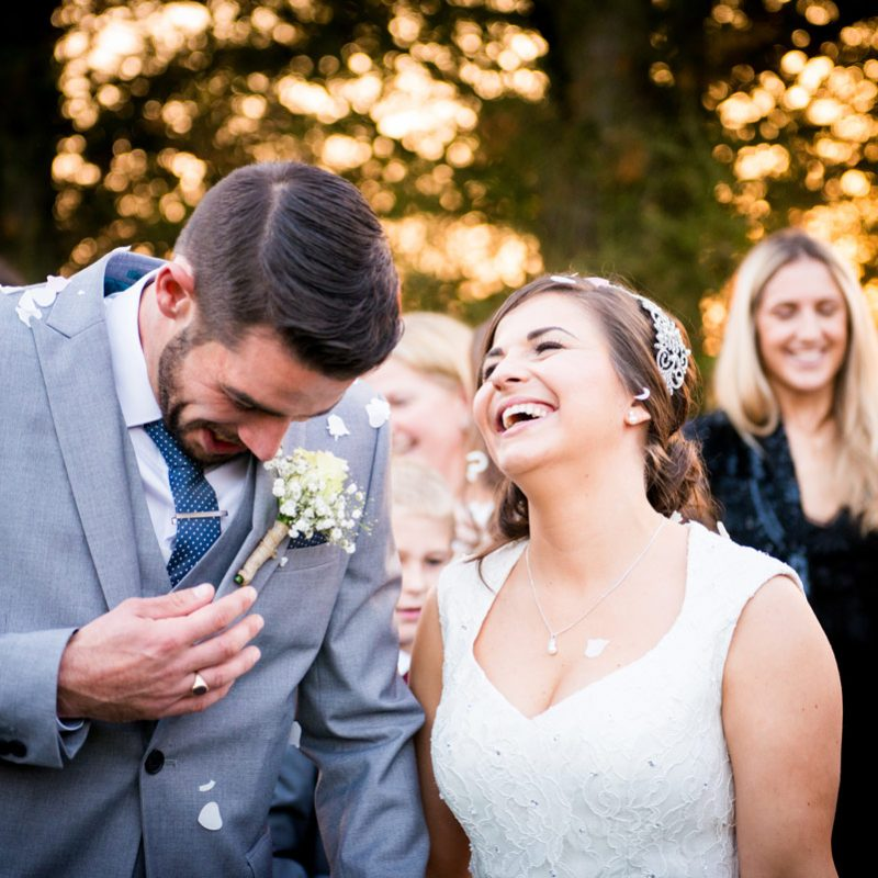 Wedding photo of bride and groom laughing after confetti