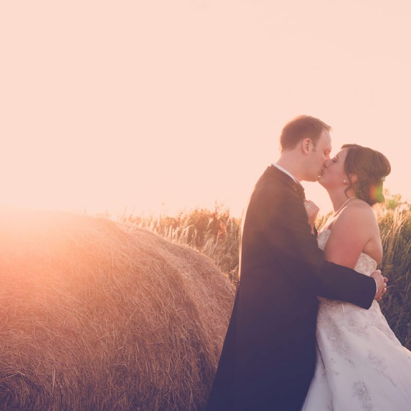 Wedding Photograph of bride and groom sunset hay bale