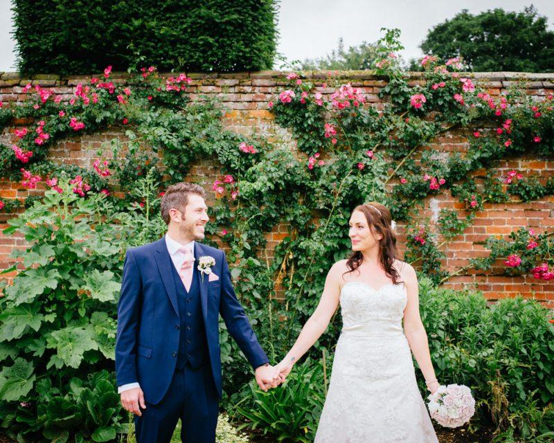 wedding bride and groom in front of garden wall