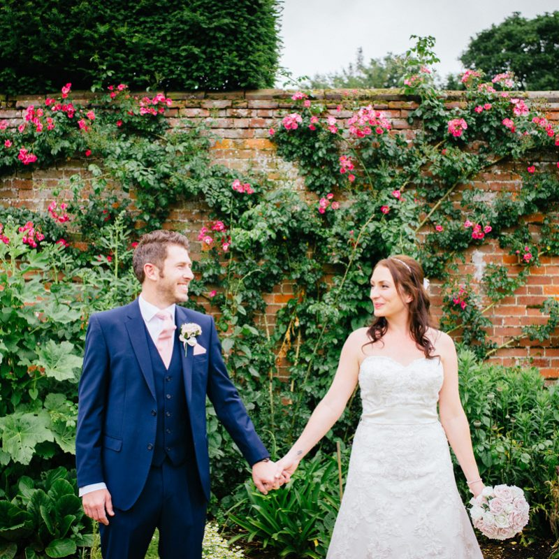 wedding bride and groom in front of garden wall