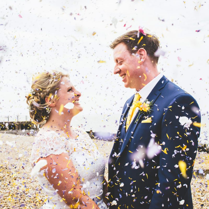 bride and groom on the beach with confetti
