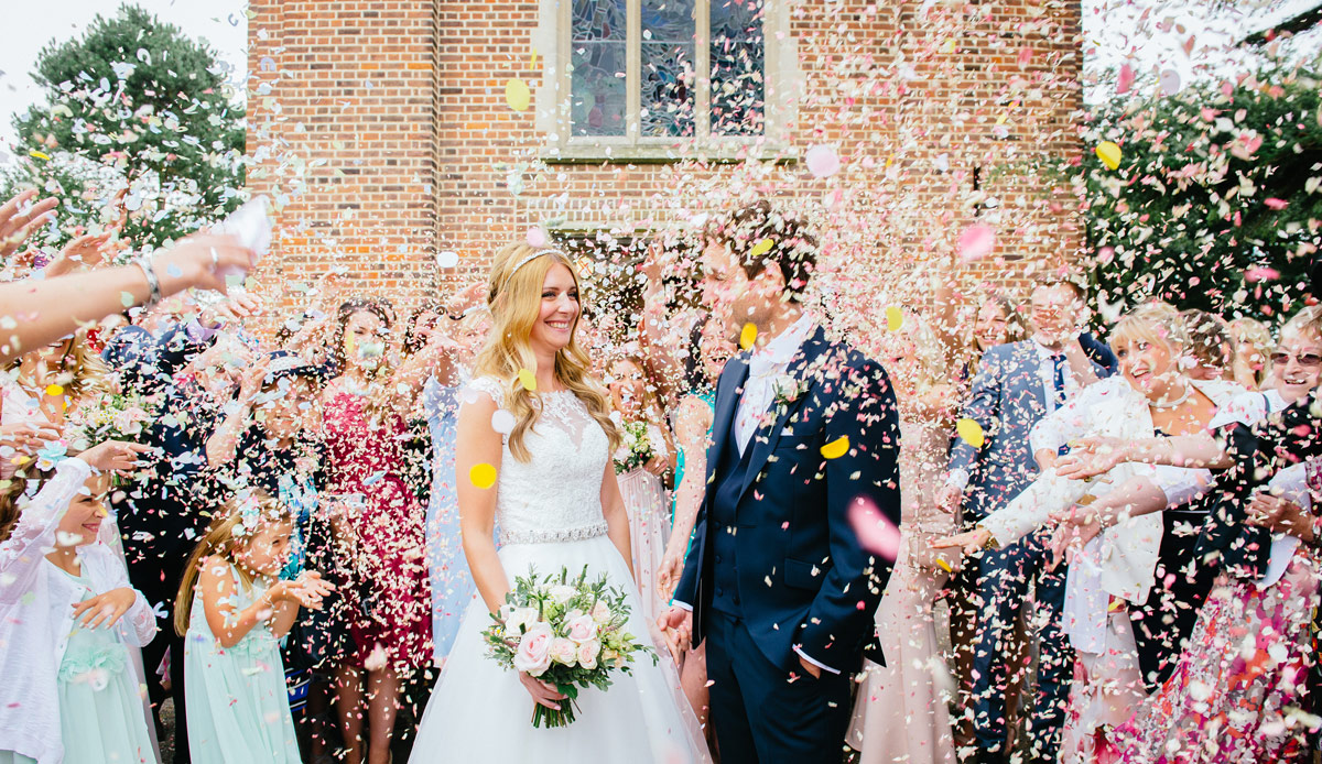wedding photograph taken at St Augustines church Thorpe bay. Bride and Groom in shower of confetti