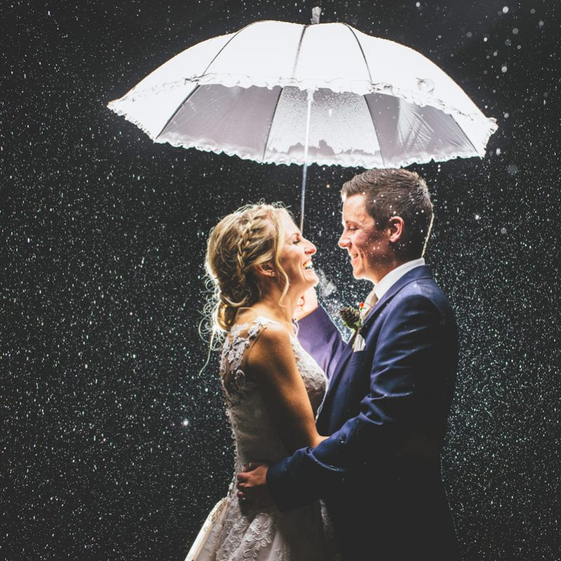 bride and groom in the rain at night with umbrella