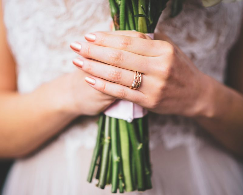 brides hands holding bouquet with rose ring