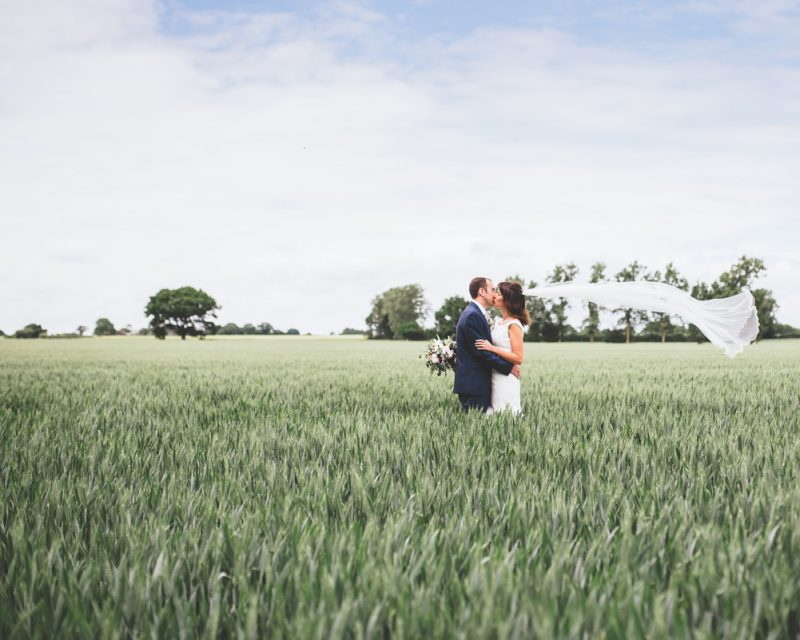 bride and groom in field at Houchins