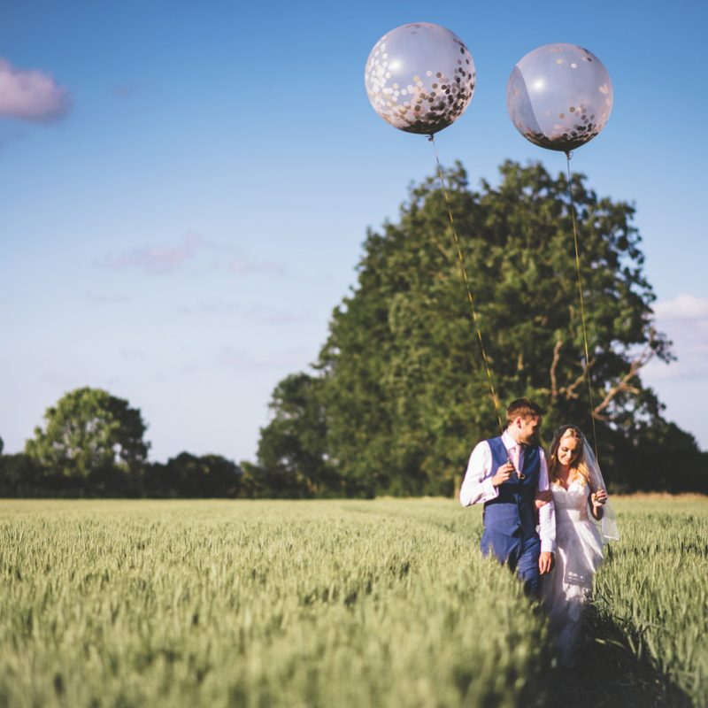 bride and groom in wheat field with giant balloons