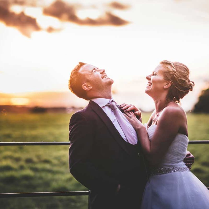 bride and groom laughing at sunset