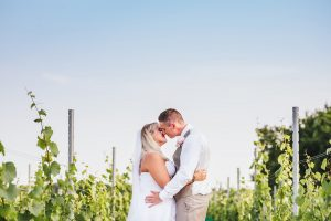 Bride and Groom standing in vineyard with blue sky